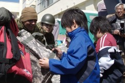 Photo : Children receive bags of friendship at the Minato Elementary School shelter.