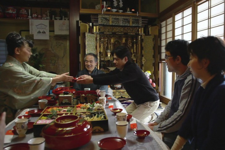 A family enjoys a typical new year's feast. Small saucers of toso (spiced sake, said to drive off ill luck) are here being served to accompany the new year's spread known as osechi ryori, an exquisitely arranged combination of seasonal foods.