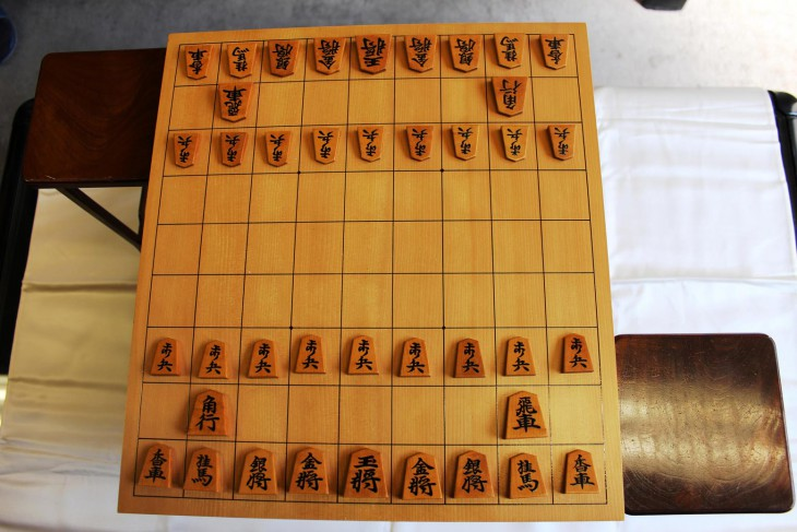 Shogi: A traditional shogi board with a set of shogi pieces in the starting setup. The stands on both sides of the board are used to hold captured pieces. COURTESY OF JAPAN SHOGI ASSOCIATION